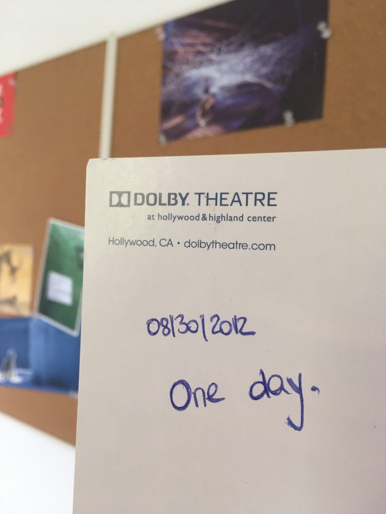 """Back of the postcard of the Kodak Theater in Los Angeles, inscription """"One day."""""""